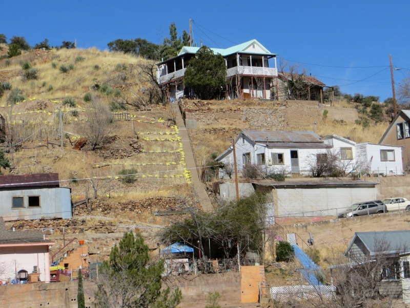 The only way to get to the houses above the street is by stair. As you can see size and state of repair of a house can vary. The yellow sandbags is where the mining company, Freeport McMorRan, removed the soil to clean it of toxins.