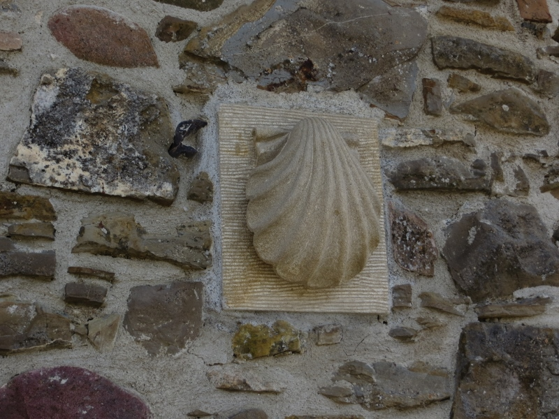 The scallop shell is the symbol of the Camino. Every pilgrim wore a shell and shells (along with yellow arrows) were on buildings to mark the route.