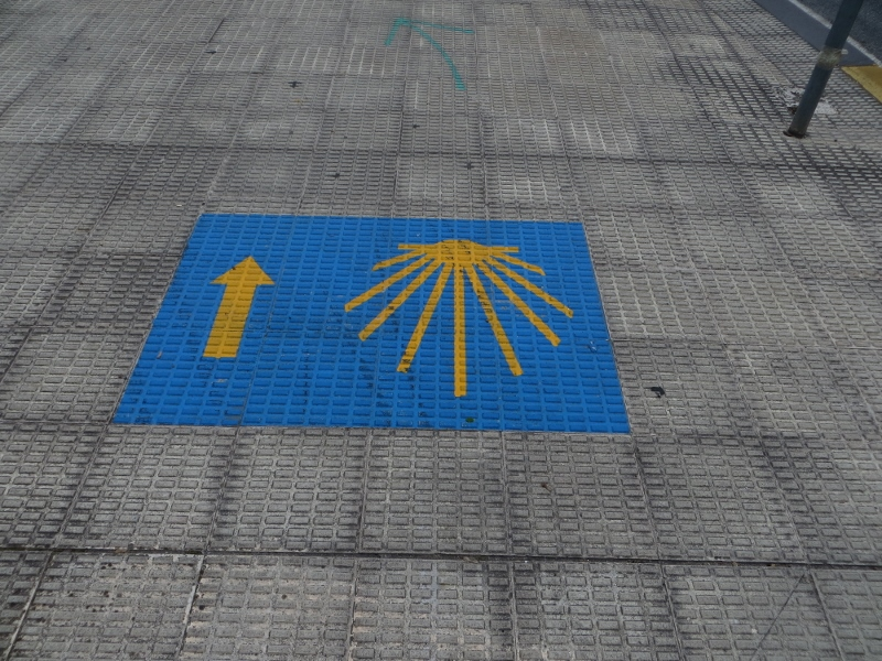 Here's an example of a stylized shell and yellow arrow on a sidewalk heading into Pamplona.